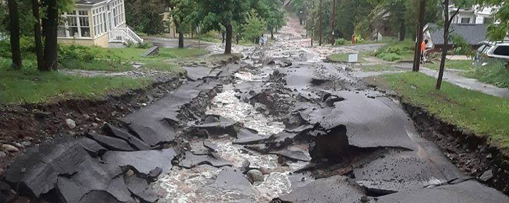 Damaged road as a result of flash flooding. See how you can help those impacted by the flooding