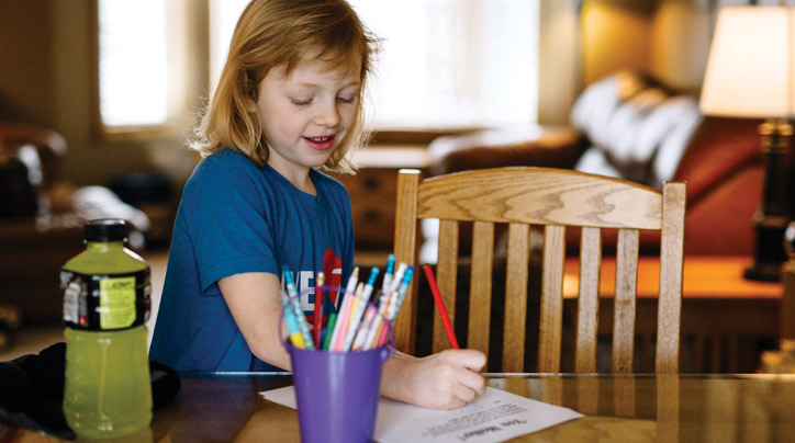 Young child writes a note for service activity.