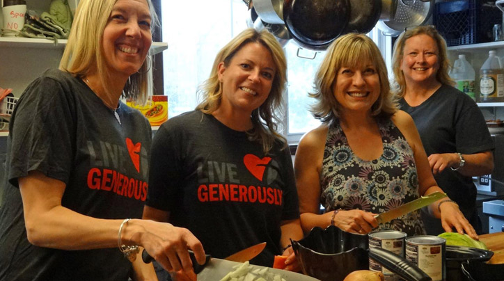 Four women cooking in kitchen as part of generosity challenge