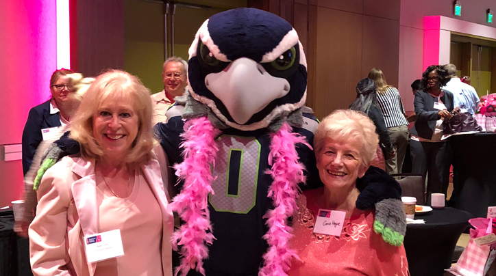 Thrivent Financial professional Sherryl Adair and Connie Hogue pose with Seattle Seahawks mascot, Blitz.